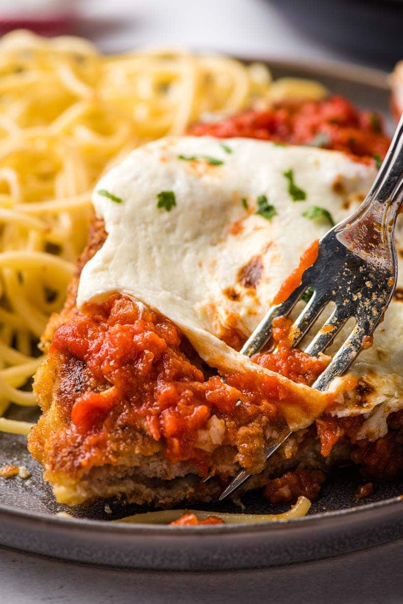 a fork taking a bite out of a piece of veal parmesan