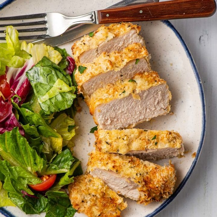 crispy pork chops sliced on a plate with green salad