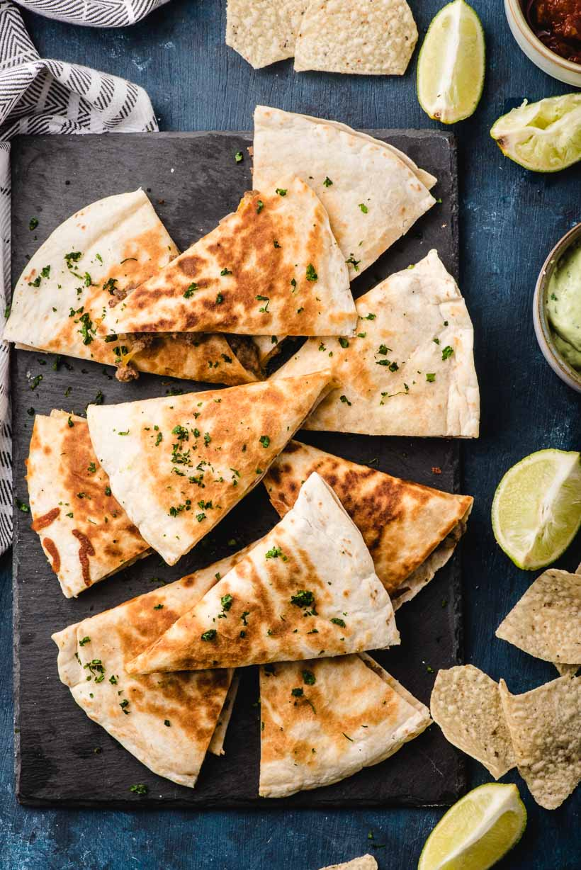 platter of ground beef quesadillas with lime and chips