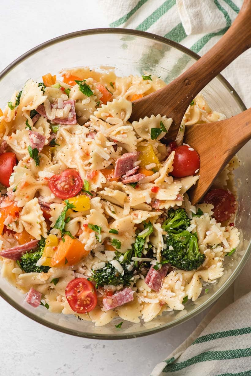 bowtie pasta salad in a glass bowl with wood serving utensils
