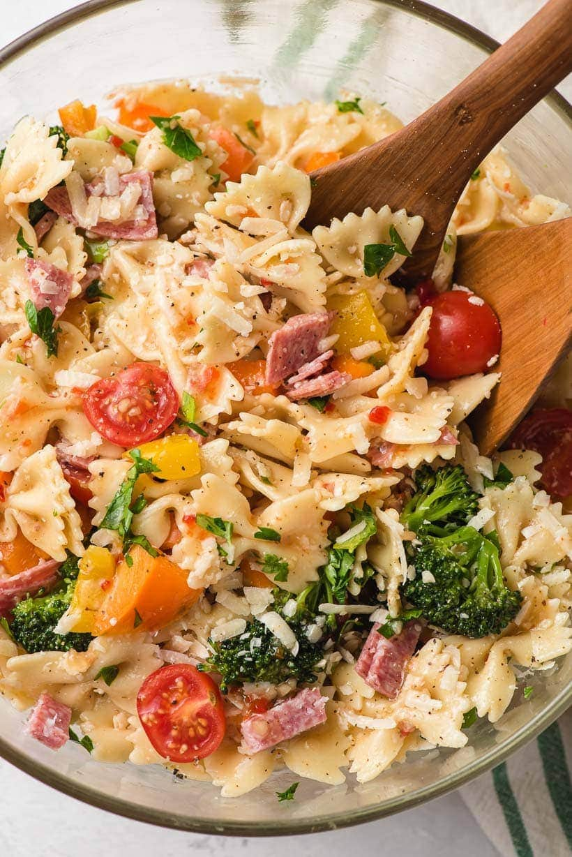 Italian bowtie pasta salad in a large bowl with wooden spoon