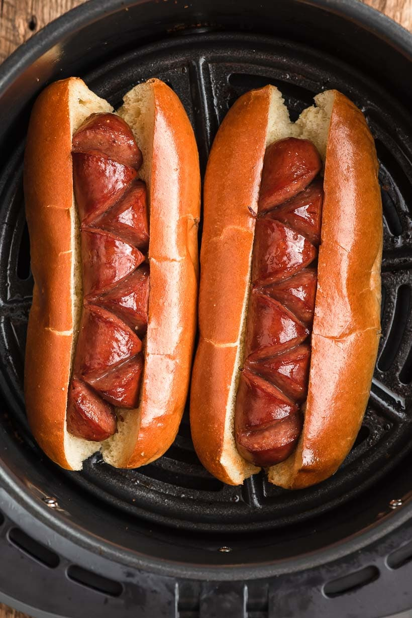 two cooked Air Fryer Hot Dogs sitting in the air fryer basket