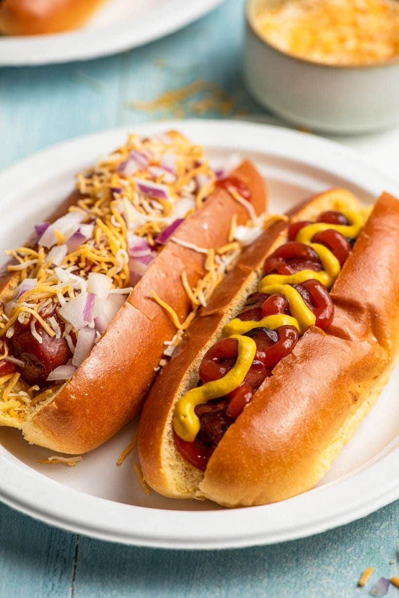 two air fryer hot dogs on a paper plate with toppings