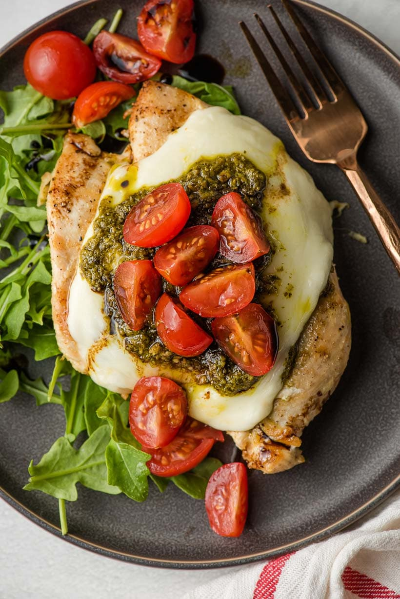 grilled chicken margherita with mozzarella, pesto, and tomatoes on top