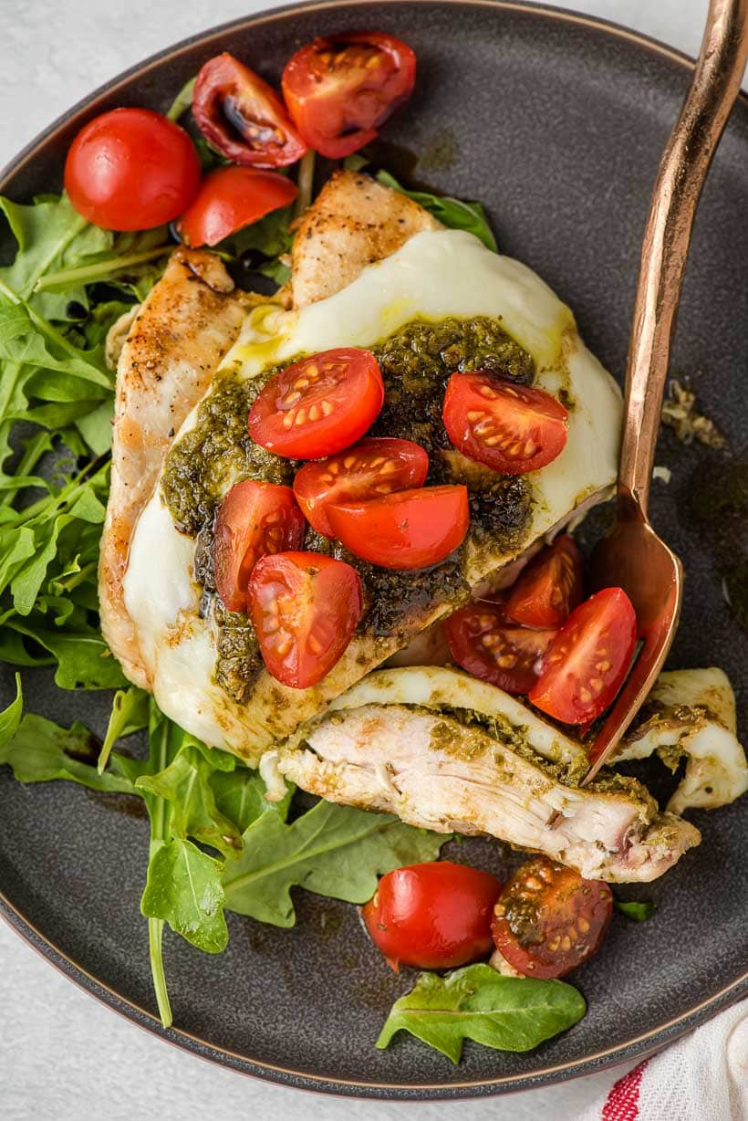 margherita chicken with a gold fork taking a bite