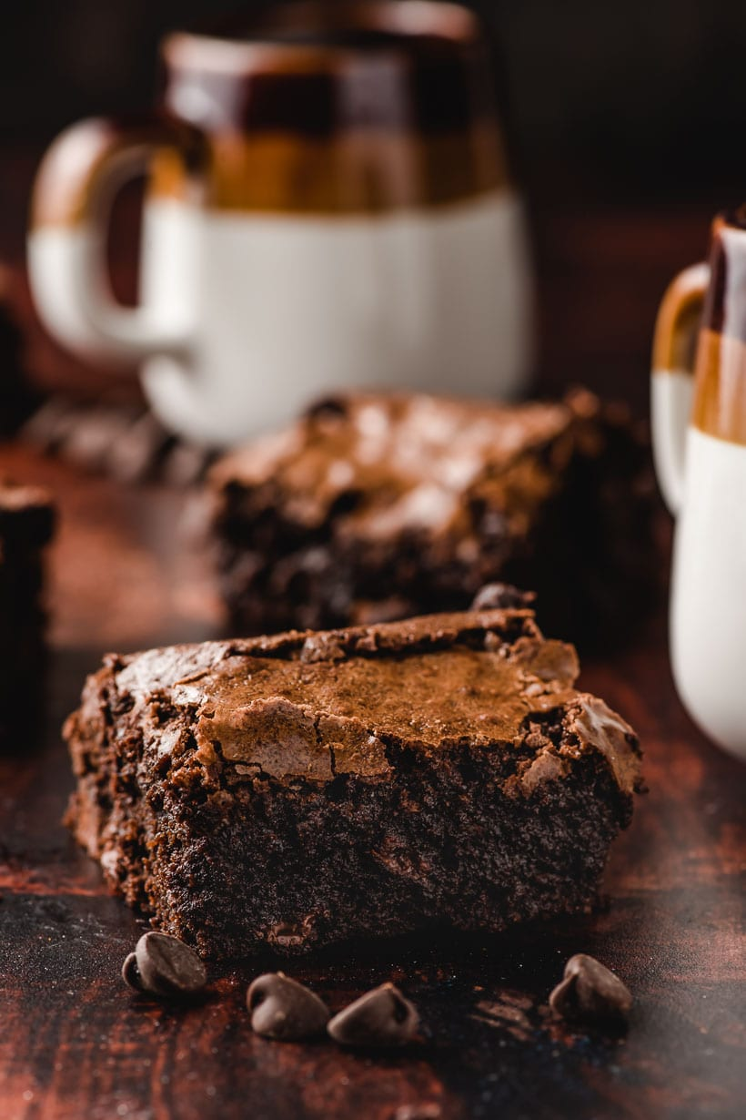 slice of homemade brownie recipe with mugs of milk