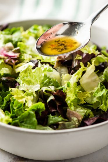 spoonful of Italian dressing recipe drizzling over salad greens