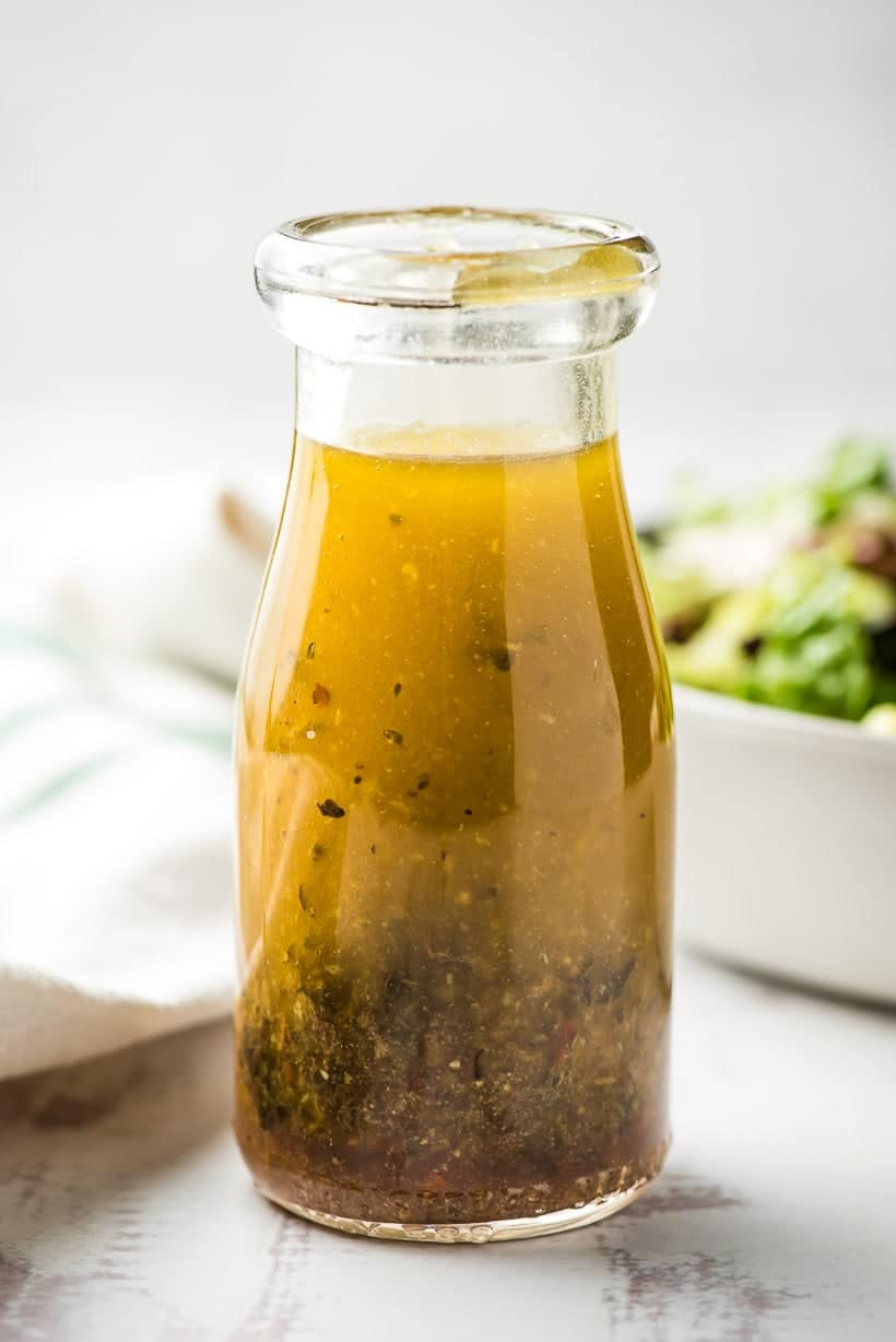 glass bottle filled with a homemade Italian dressing recipe