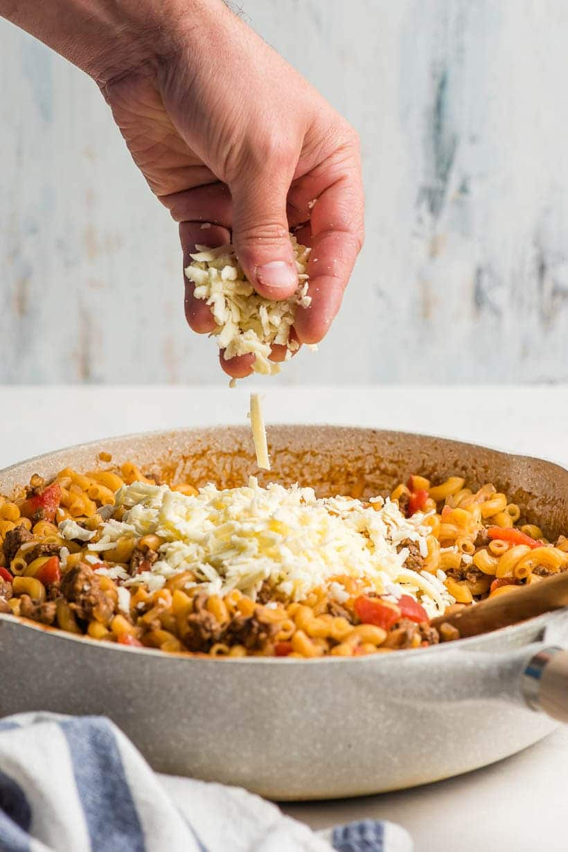 hand sprinkling cheese on cheeseburger pasta
