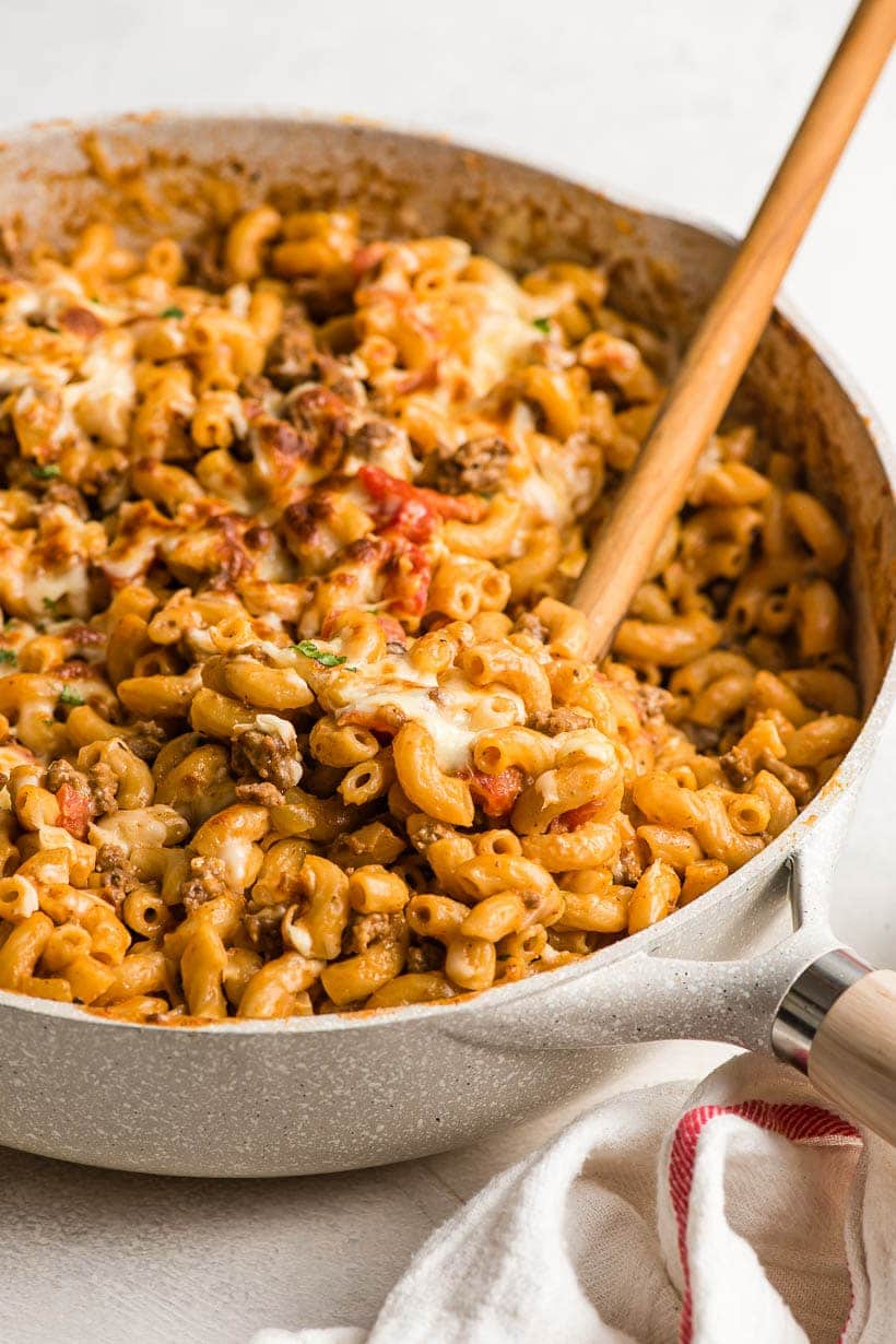wooden spoon dipping into pot of cheeseburger macaroni