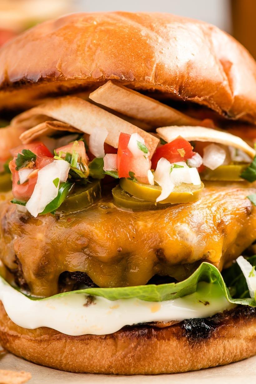 up close shot of taco burger with pico de gallo and sour cream