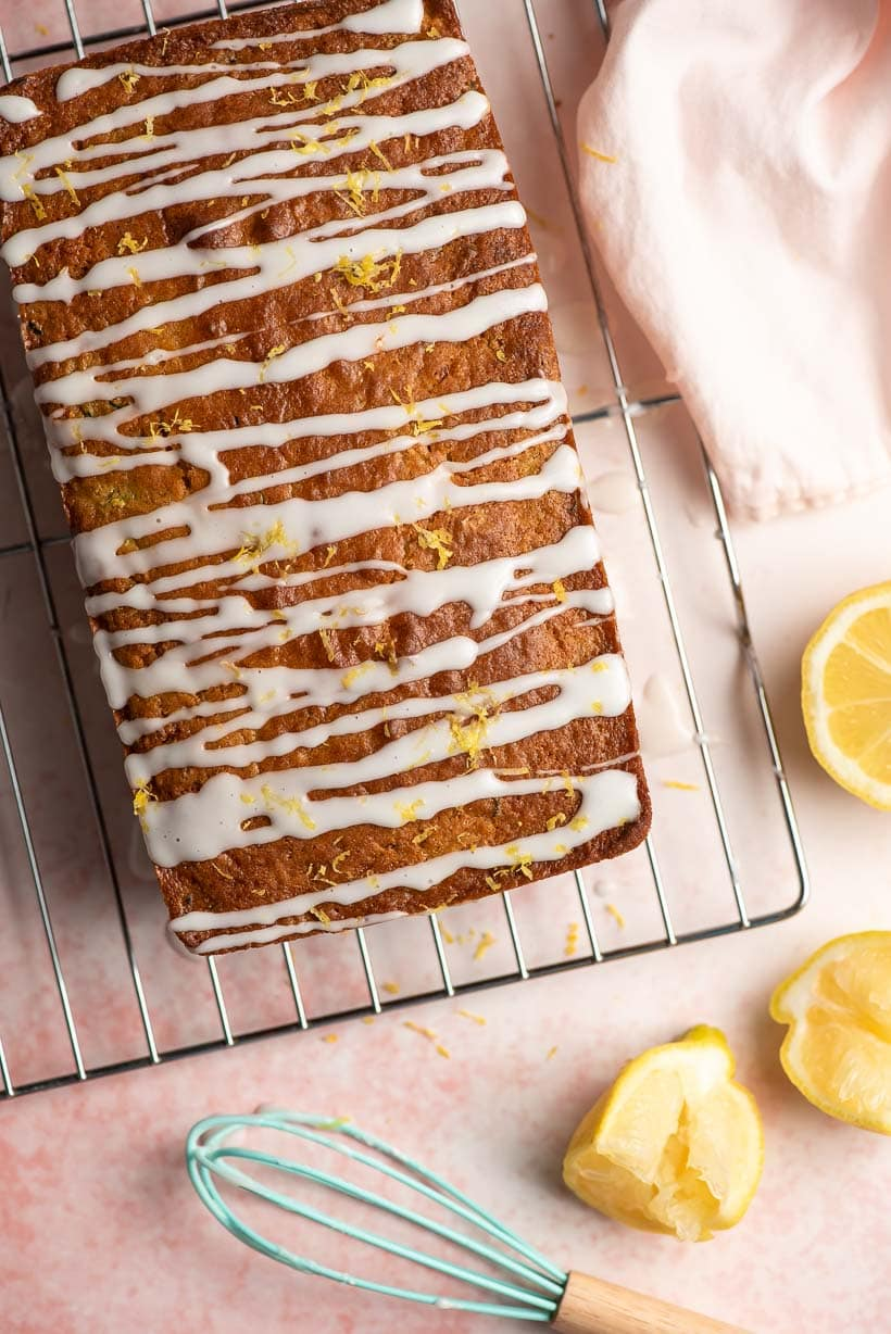 lemon zucchini loaf with whisk and squeezed lemon halves