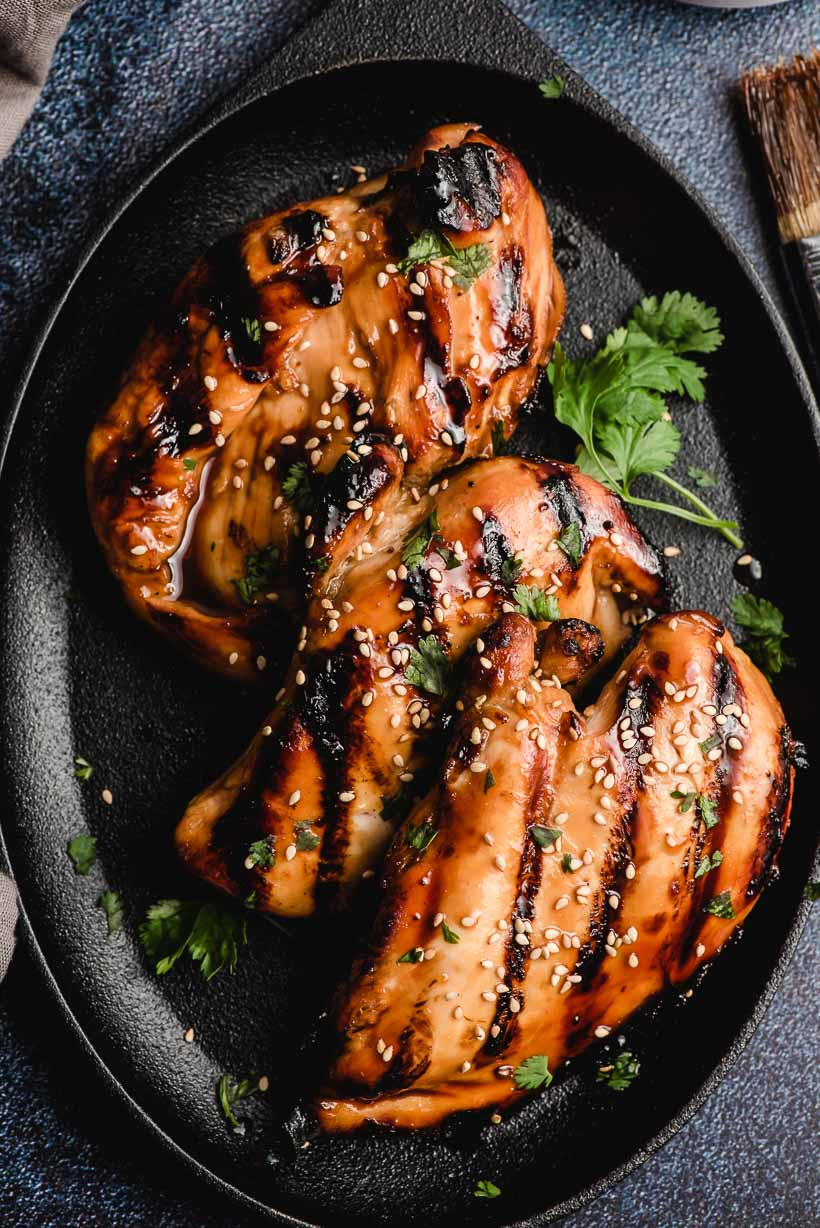 3 grilled chicken breasts on a skillet coated with Asian chicken marinade sauce and sesame seeds