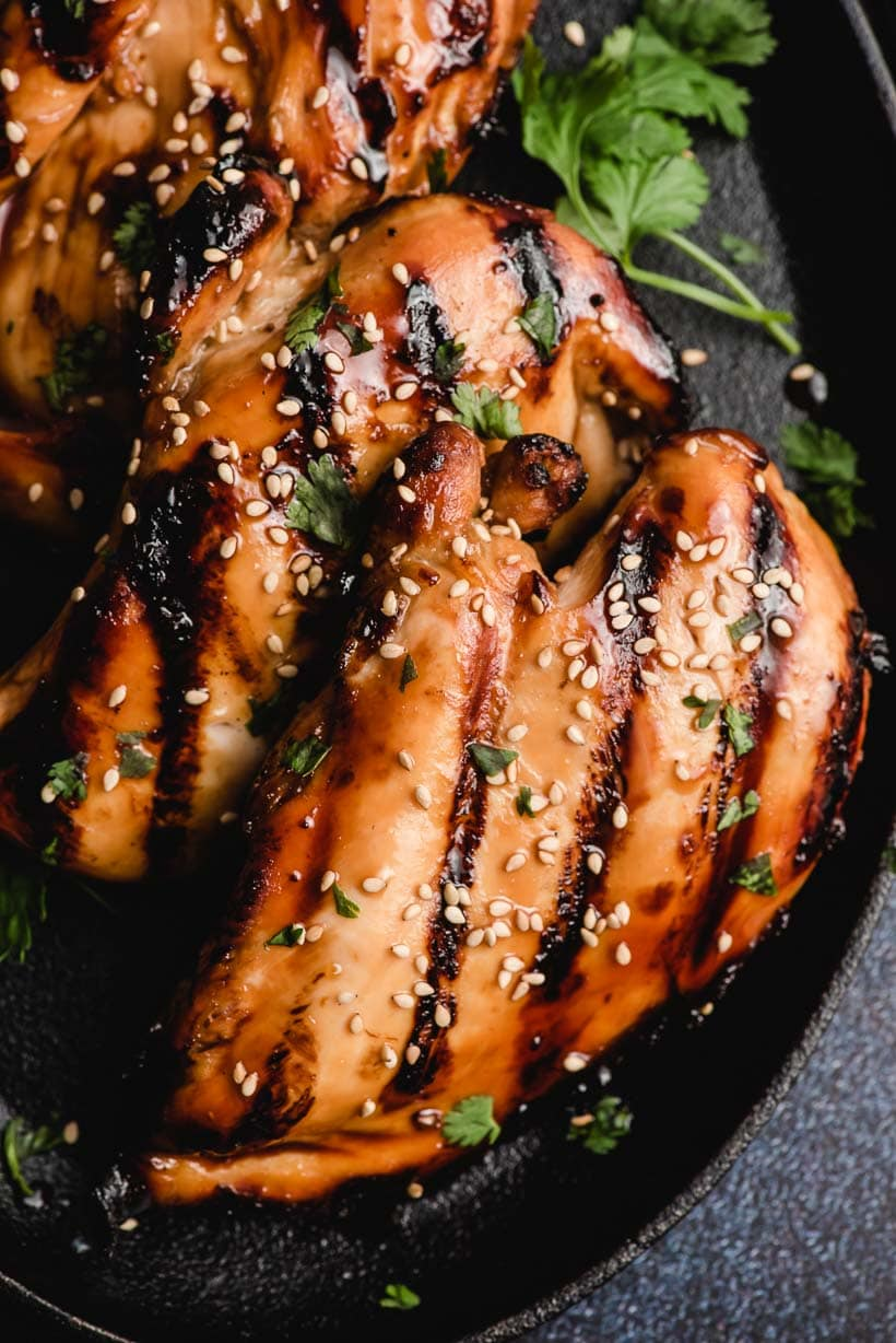 grilled chicken breast coated with sesame seeds and asian chicken marinade sauce on a skillet