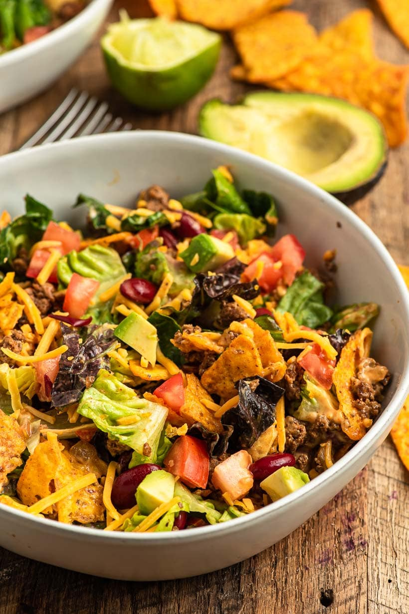a bowl of my doritos taco salad recipe with ingredietns in the background