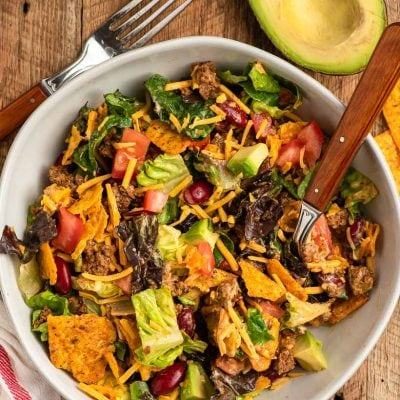a bowl of doritos taco salad next to a sliced avocado