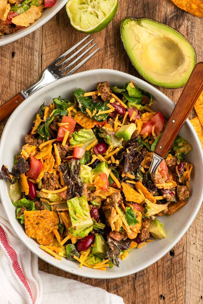 a bowl of doritos taco salad sits on a table next to a sliced avocado