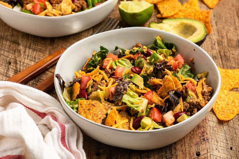 a bowl of doritos taco salad sits on a table with napkin and other ingredients