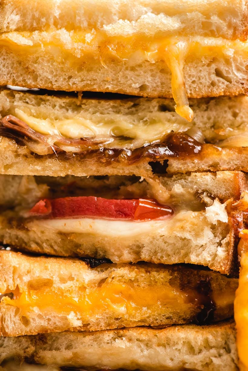 up close stack of grilled cheese with different fillings