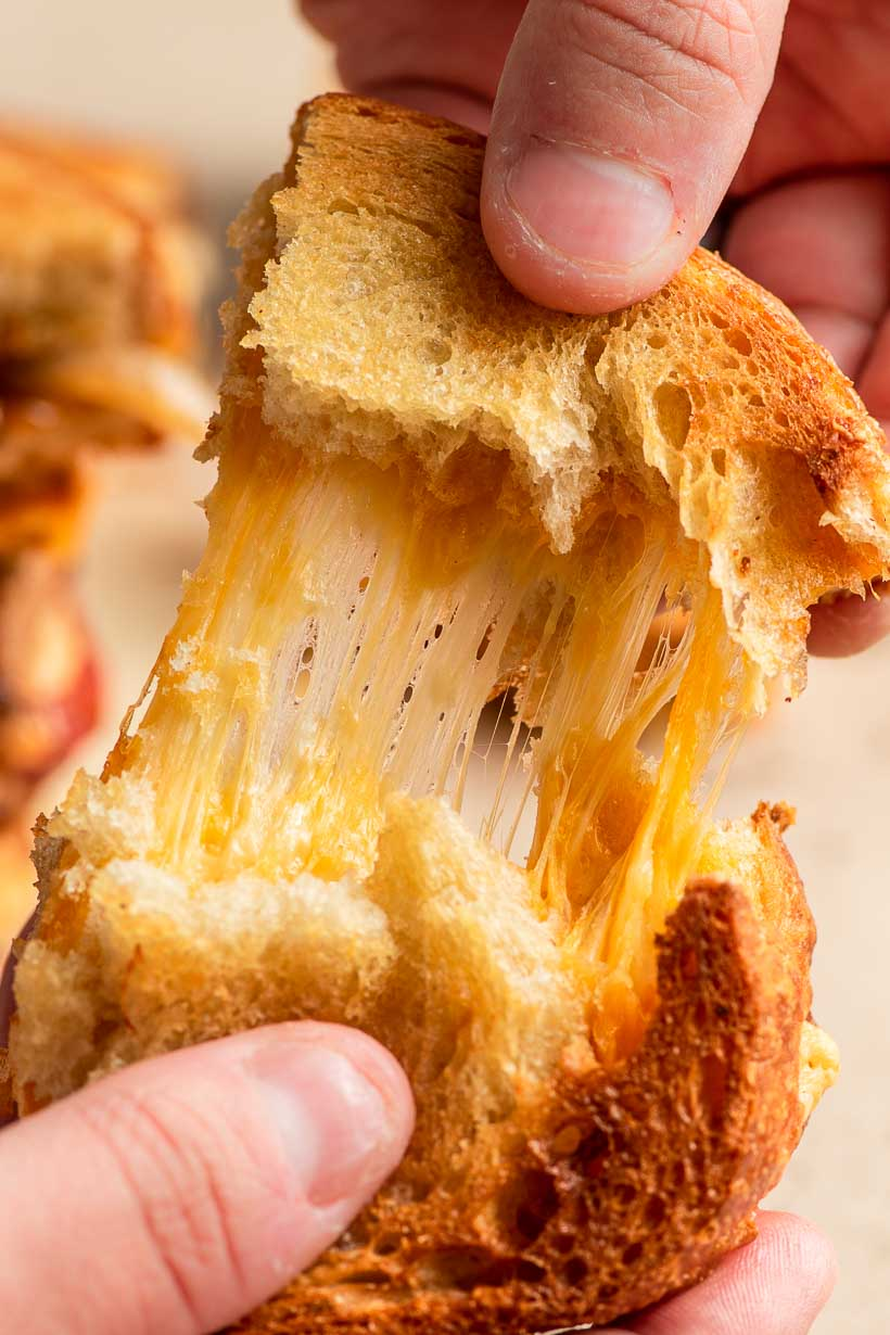 hands pulling apart an air fryer grilled cheese