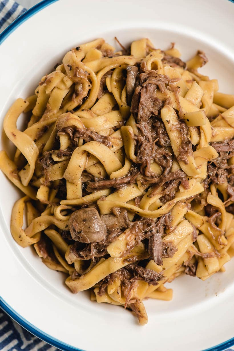 shredded beef and noodles in a white bowl
