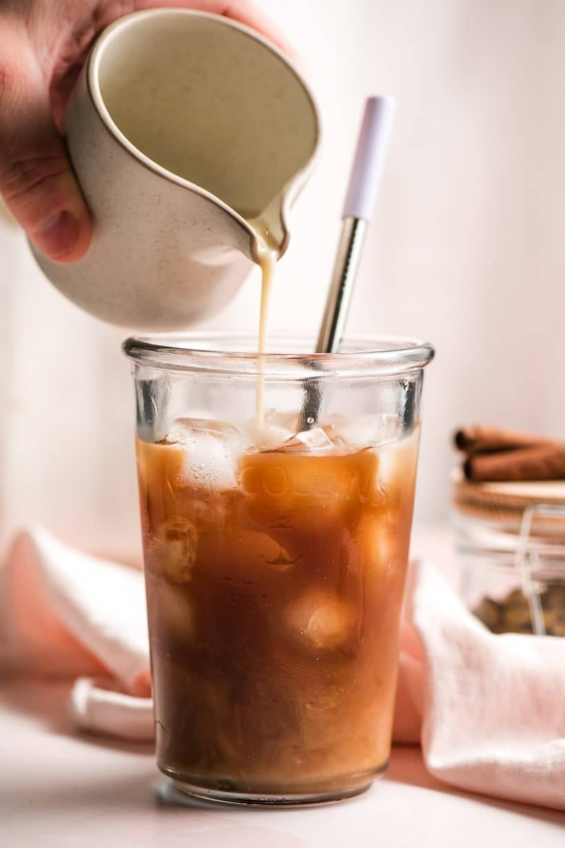 milk poured into a glass of iced chai concentrate