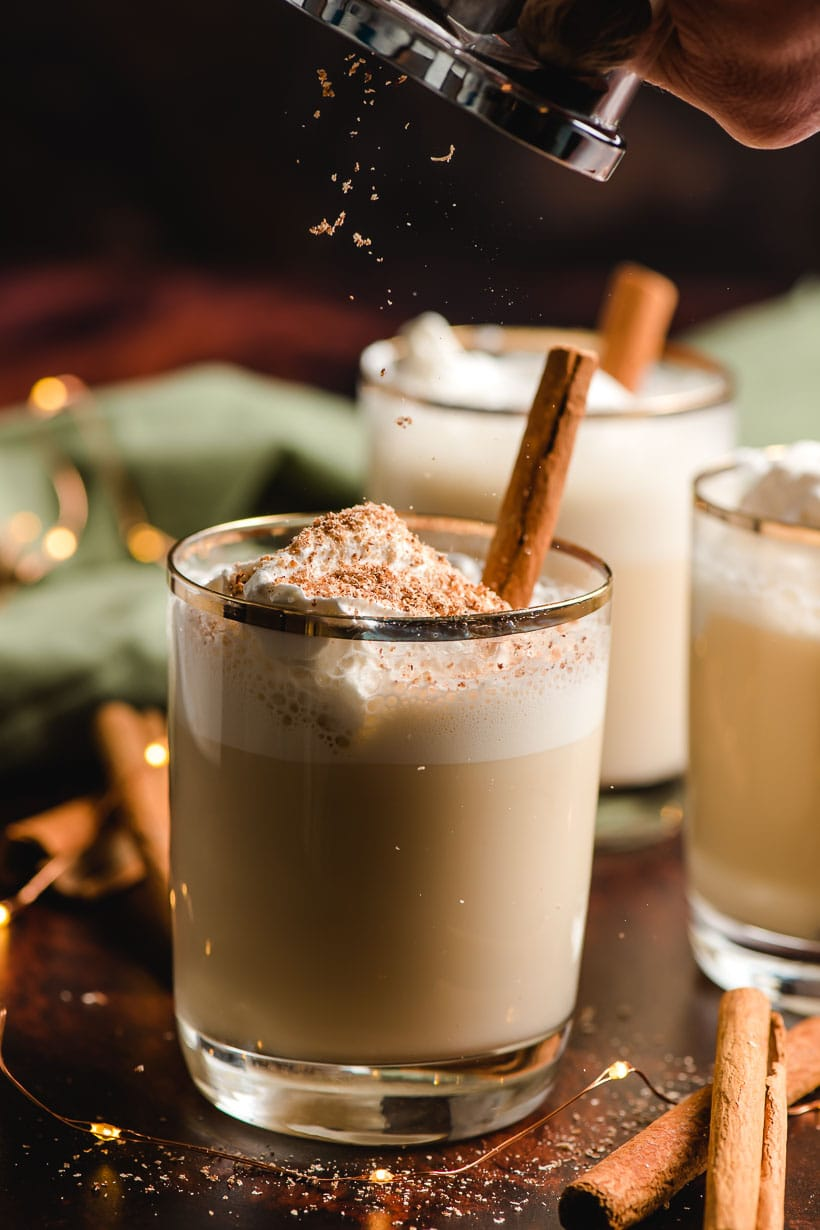 nutmeg being grated onto a glass of eggnog