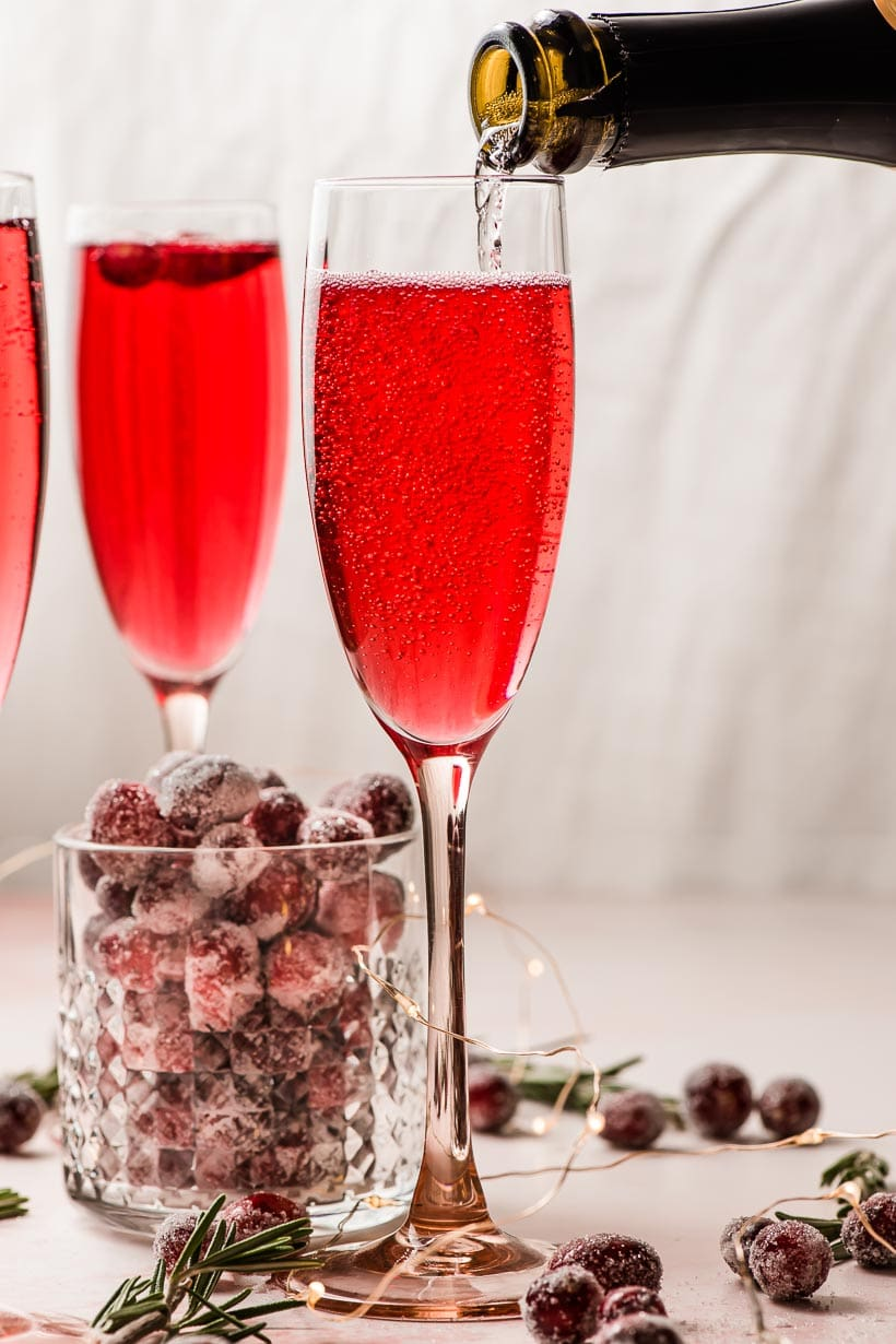 prosecco being poured into a glass of cranberry juice