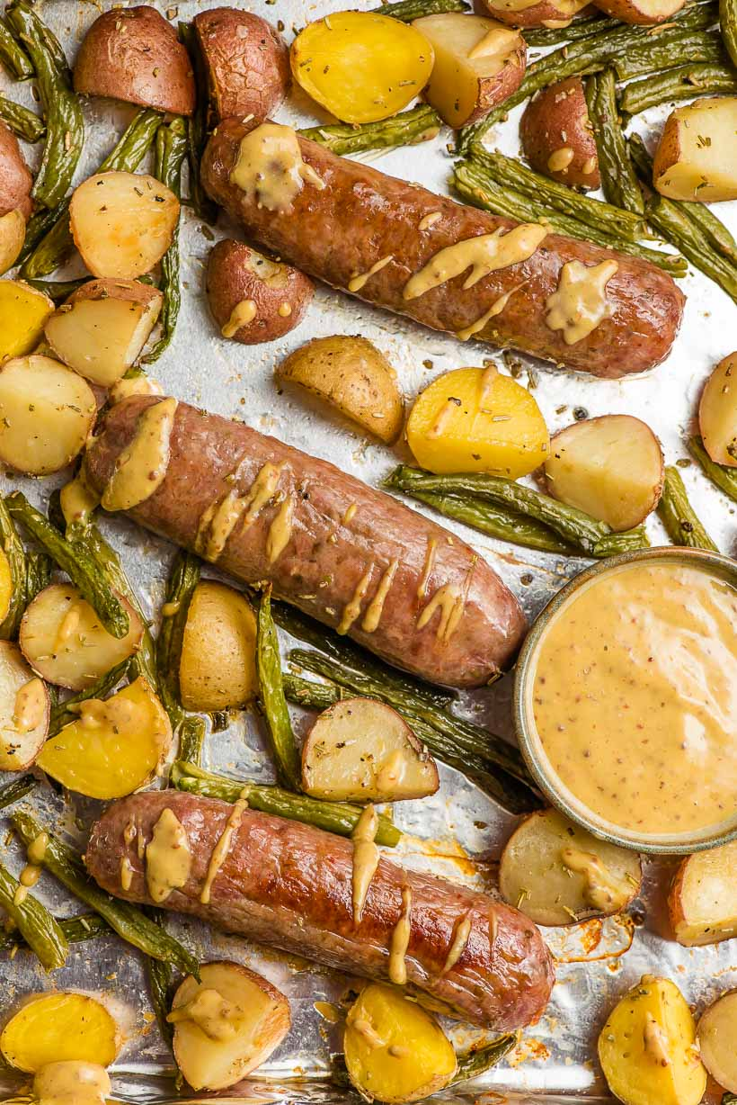 baked italian sausages and potatoes with dijon sauce drizzled on top
