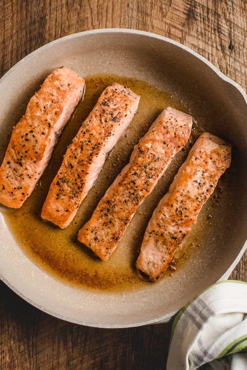 pan full of seared salmon fillets