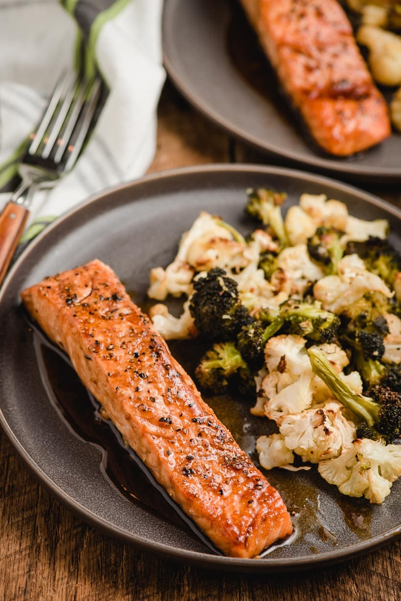 pan seared salmon on a plate with roasted broccoli and cauliflower