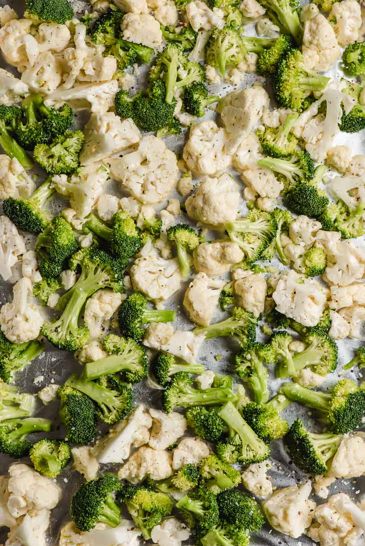 raw broccoli and cauliflower florets on a baking sheet
