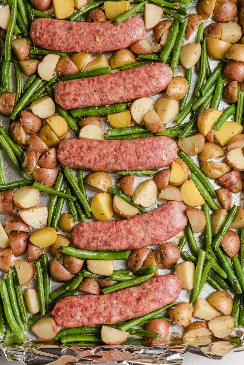 italian sausage links, green beans, and potatoes on a sheet pan