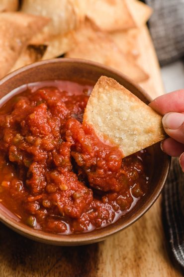 Hand grasping a tortilla chip dipping into a bowl of salsa.