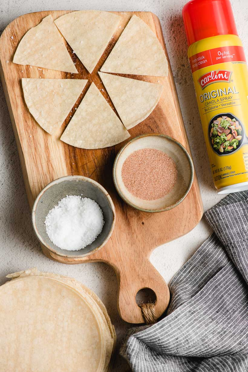 Cutting board with a corn tortilla cut into wedges on top, plus bowls of salt, cinnamon sugar, and cooking spray.