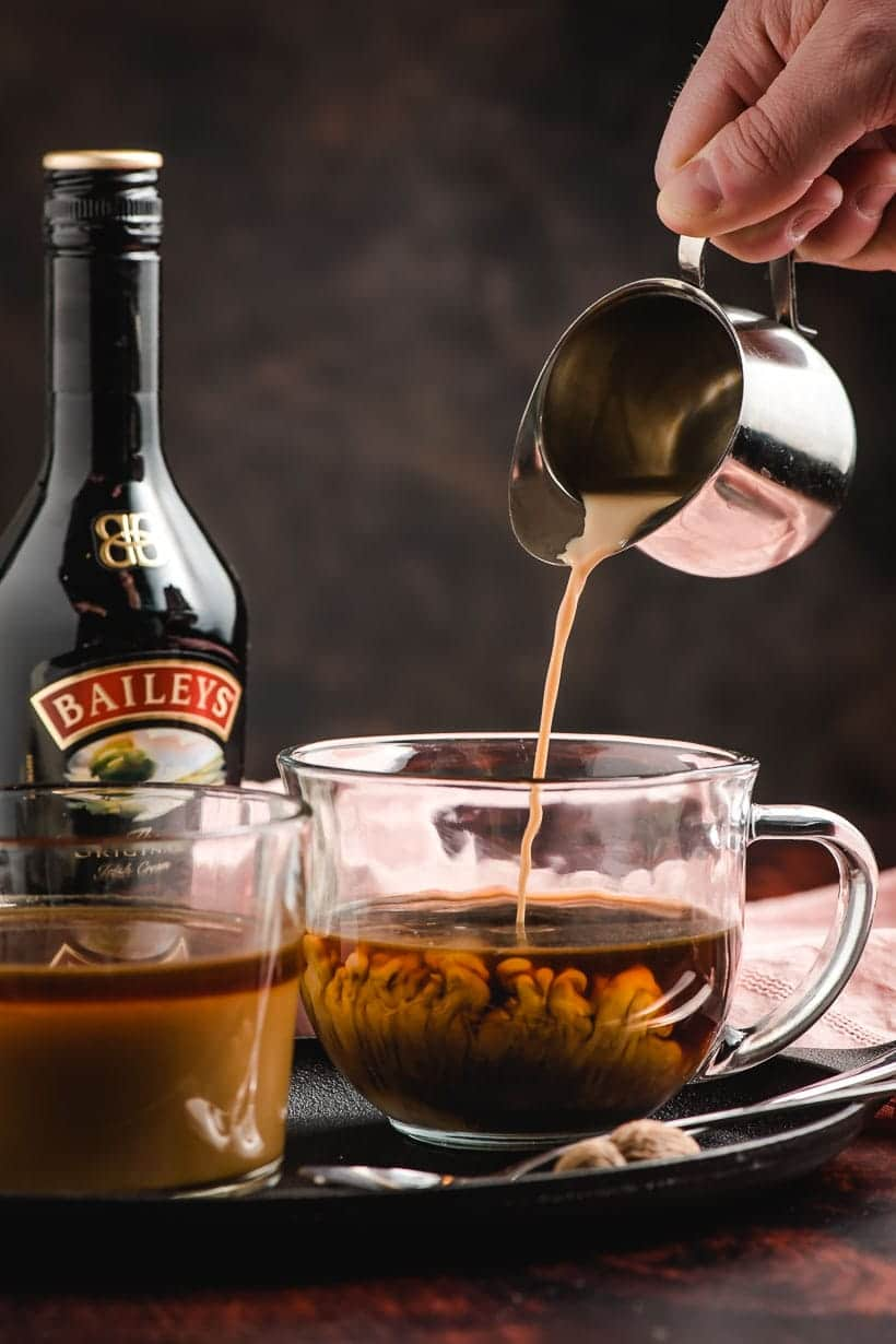 Metal pitcher pouring Bailey's Irish cream in coffee, with swirls of cream billowing up into the coffee.