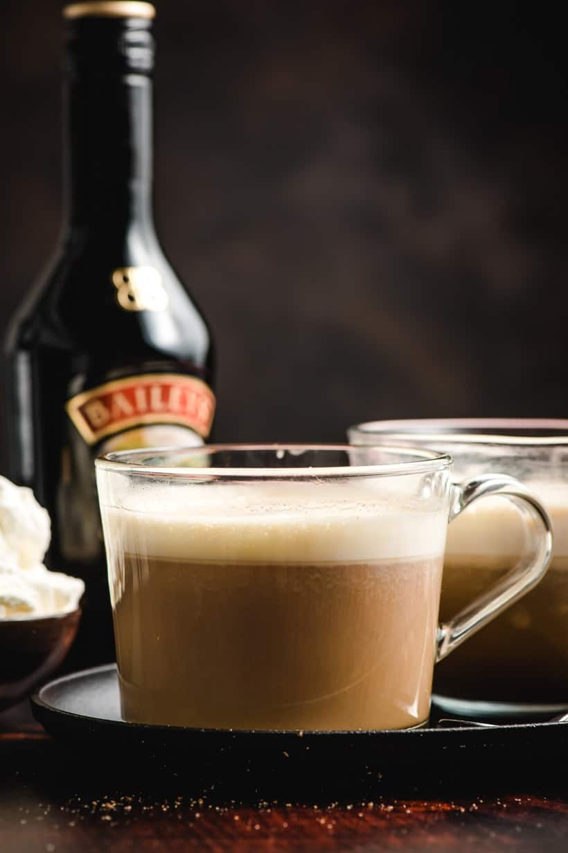 Glass mug filled with Irish Coffee with bottle of Bailey's Irish Cream in the background.