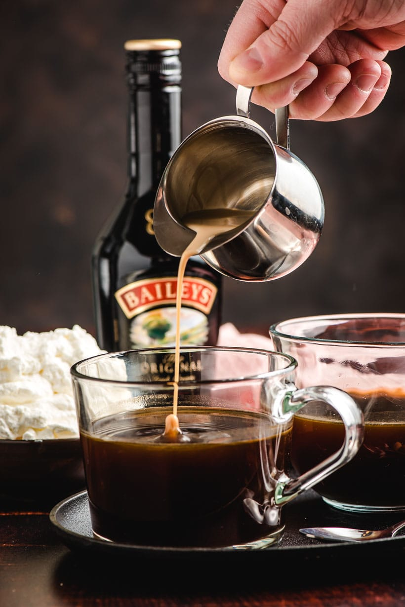 Small metal pitcher pouring Bailey's Irish cream into a cup of coffee.