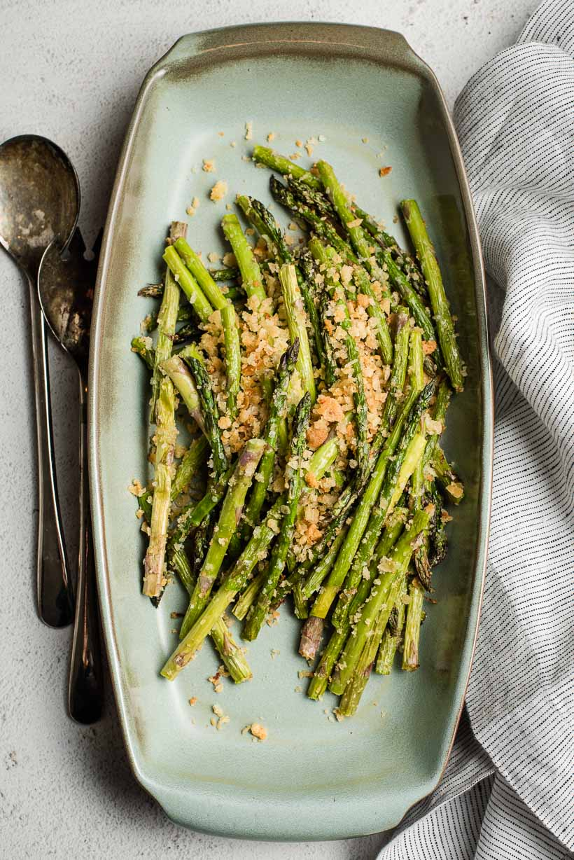 air fryer asparagus topped with breadcrumbs on a large oval serving platter