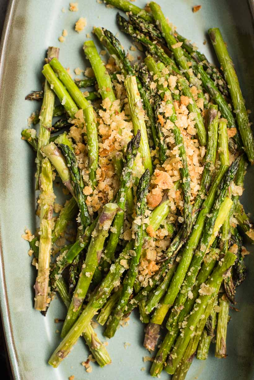 Air fried asparagus with breadcrumbs on a blue gray platter.