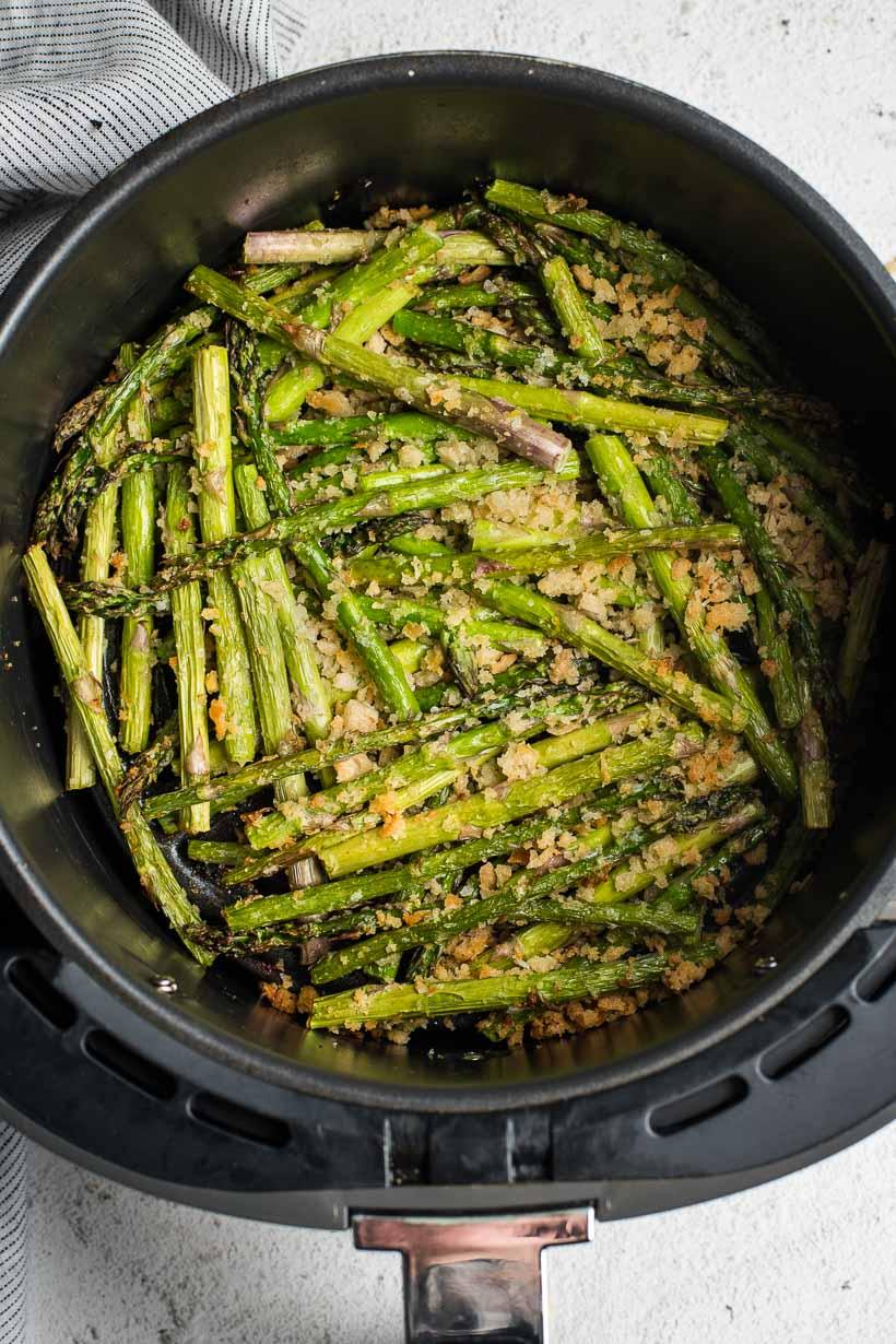 Halved asparagus stalks in an air fryer basket with breadcrumbs.