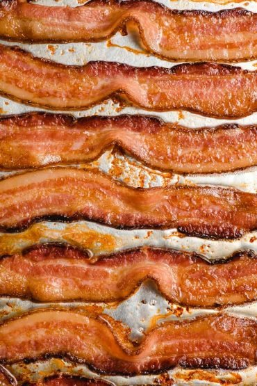 Slices of crispy oven baked bacon on a baking sheet.