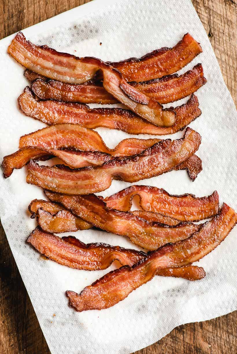 Cooked bacon slices draining on a paper towel lined platter.