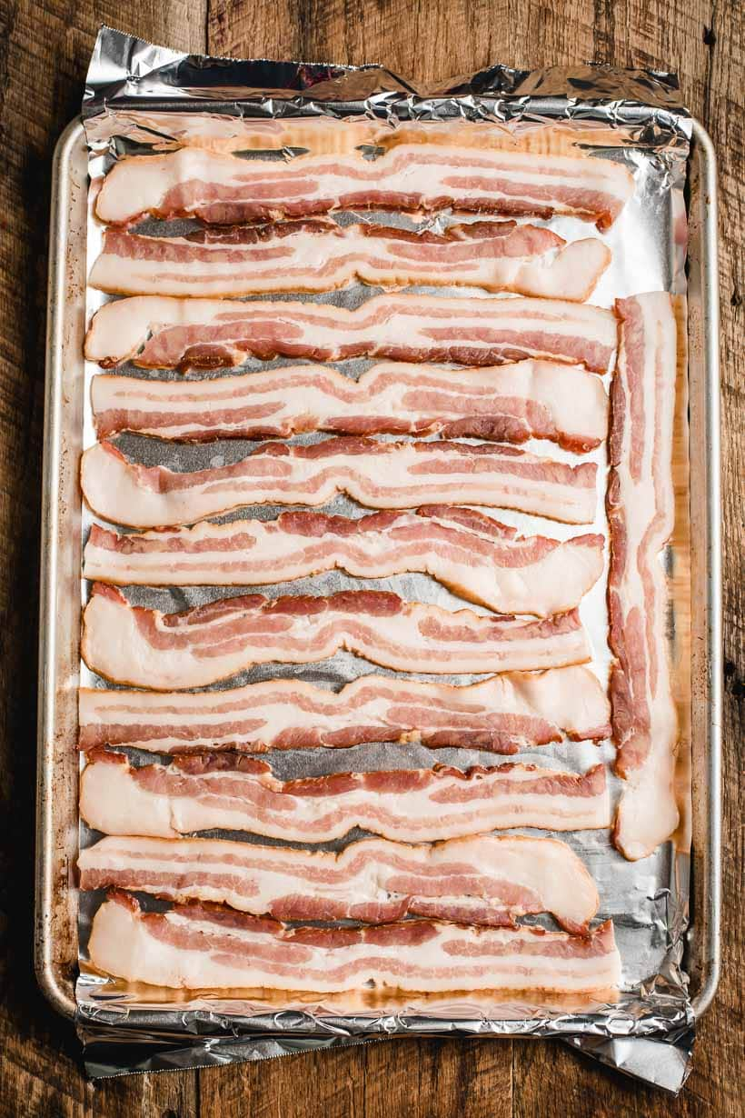 Slices of raw bacon on a foil lined baking sheet.