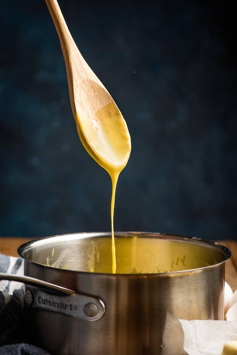 Wooden spoon drizzling hollandaise into a sauce pot.
