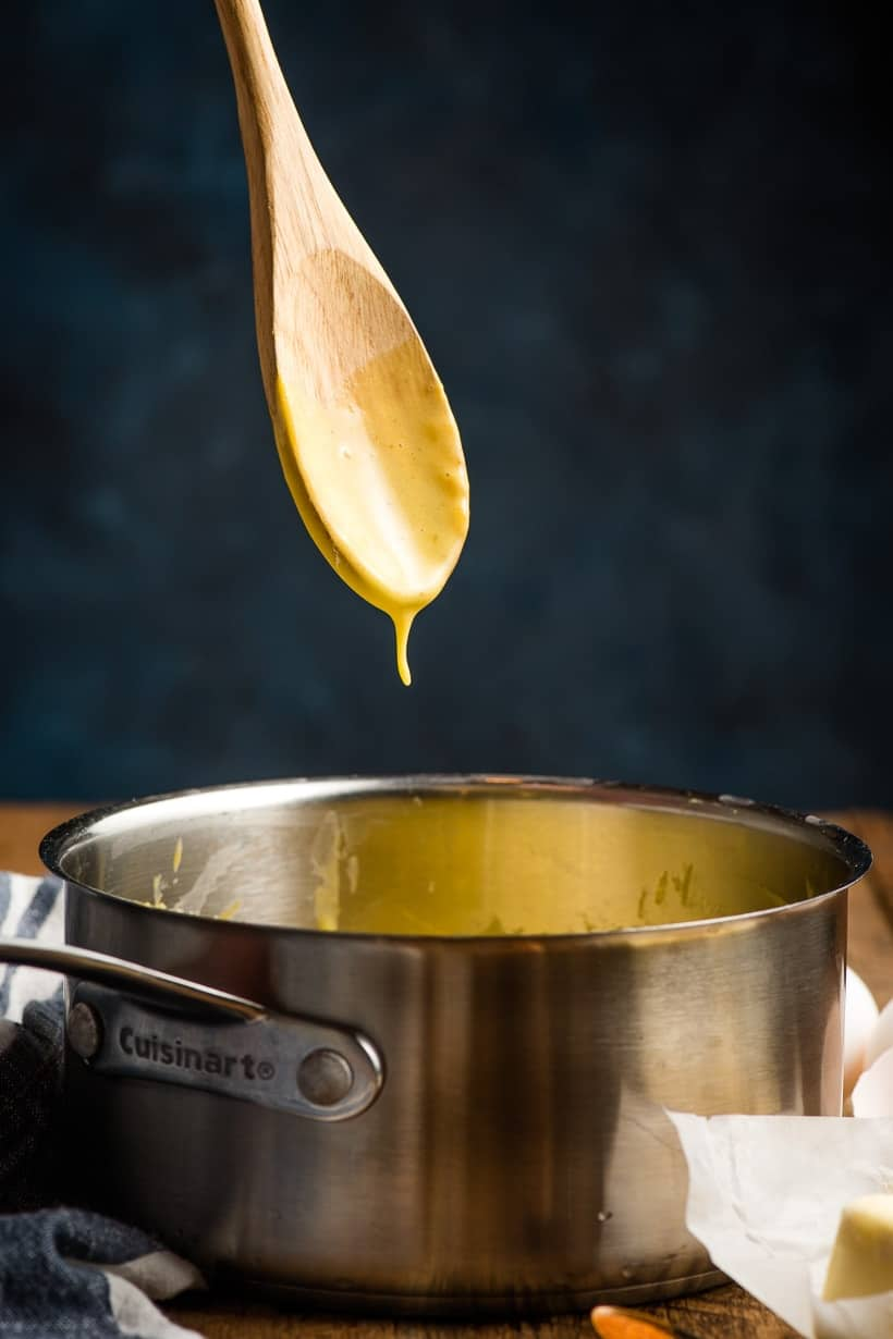 Drip of hollandaise sauce coming off of a wooden spoon.
