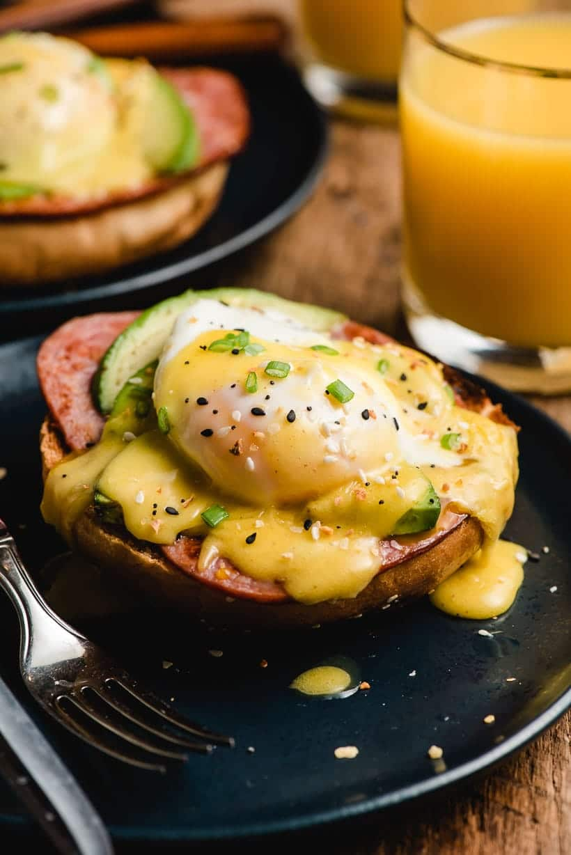 Navy blue plate with ham, avocado, poached egg, and hollandaise sauce.