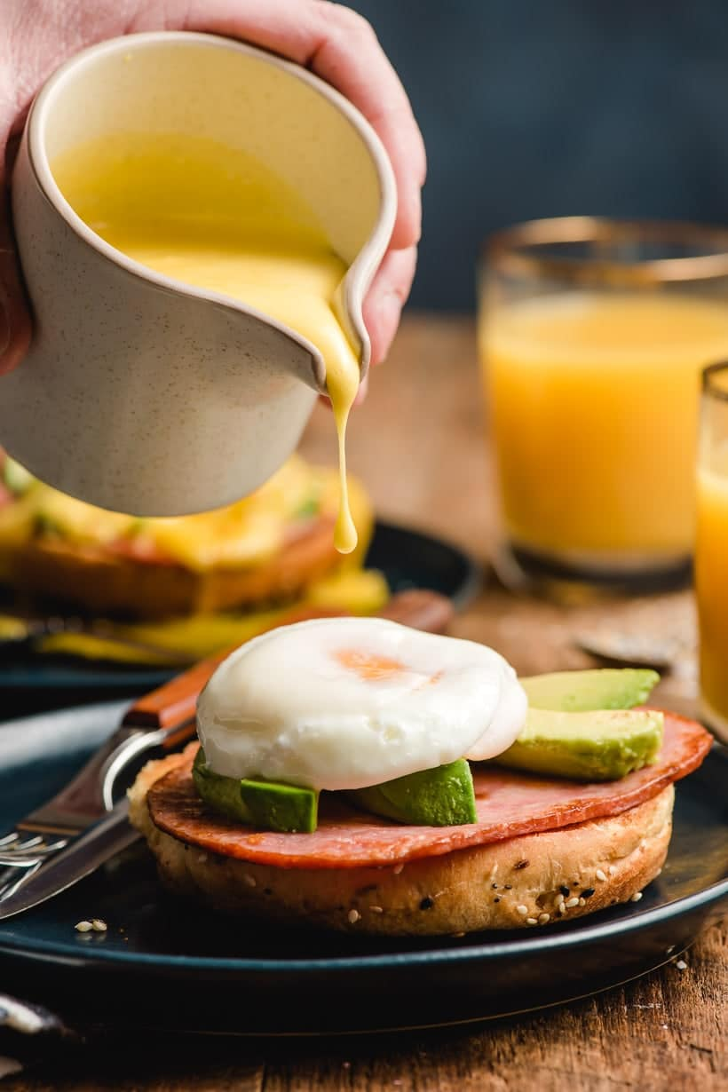 Pitcher pouring hollandaise sauce on top of Eggs Benedict.
