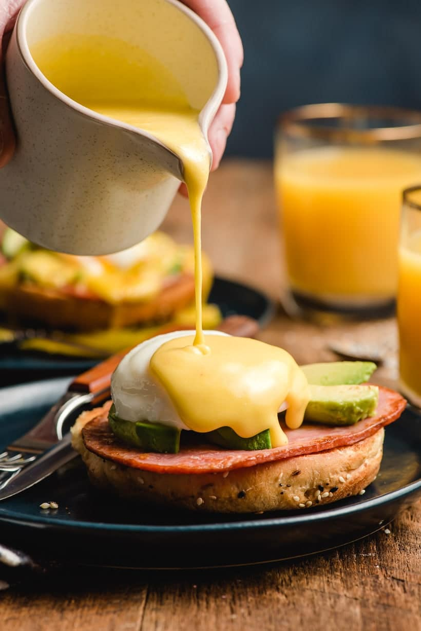 Hollandaise sauce being drizzled from a pitcher over Eggs Benedict.