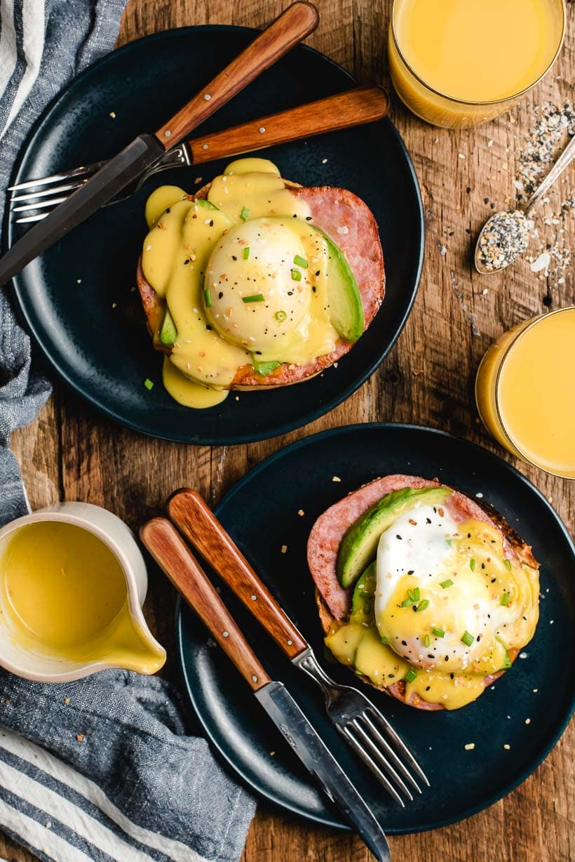 Two plates with Everything Bagel Eggs Benedict, plus a pitcher of hollandaise sauce, and two glasses of orange juice.